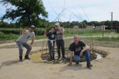 Les jeunes de l'ITEP et leurs éducateurs près de leur cabane en saule tressé